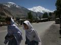 Scholars walk along a road in Hunza.